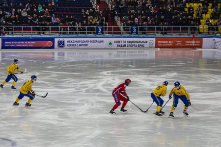 Khabarovsk  Russia - 01.31.2018: Bendy, World Championship. On the ice arena players in yellow and red uniforms. In the background stands with spectators. Editorial