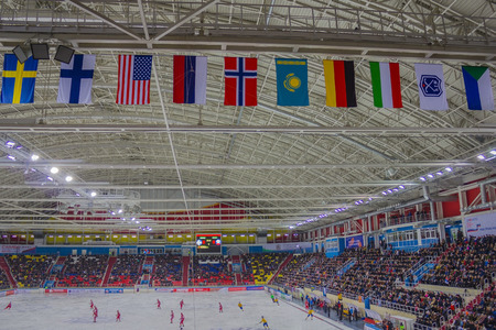 Covered ice arena, panorama, top view. On the field is the game, filled the stands. Under the ceiling are colored flags of the championship participants.