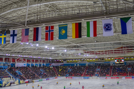 International Bandy tournament, World Championship, the middle of the match. In the foreground flags of national teams. Tribunes filled, away scoreboard with the result of the game.