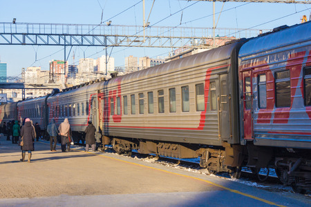 On the platform the passenger train is ready for departure. Around people in warm clothes, the weather is cold. In the distance, high modern buildings. A clear, sunny day. Editorial
