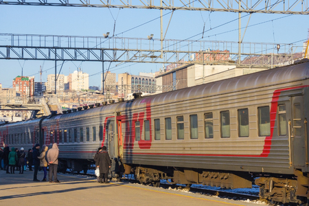 A railway station, people are walking around. The train is waiting for departure. Soft sunlight, cold season. In the distance, high modern buildings. The blue cloudless sky.