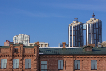 An old red brick building, green roof. Behind it, modern skyscrapers. Cityscape, various architectural styles. A blue cloudless sky, a sunny day. Reklamní fotografie