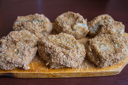 Home-made cutlets, meat semi-finished. The meatballs lie on an old, vintage cutting board made from natural wood. Warm tint.