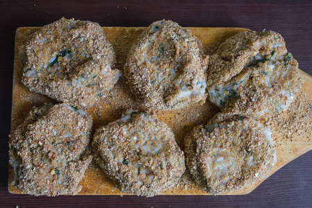 The meatballs are hand-molded, tasty homemade food. There are six raw cutlets on a wooden board. Uneven, unequal shape. Daylight. Stock Photo