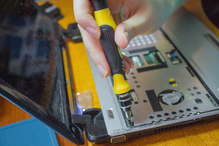 A hand with a yellow screwdriver twists the inside of the computer. Disassembly netbook, self-repair at home. Daylight. 스톡 콘텐츠
