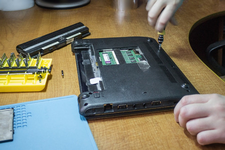 Determine the cause of breakage at home. Replacement of internal parts, preventive works. The black netbook is disassembled with a screwdriver. Brown table, artificial lighting.