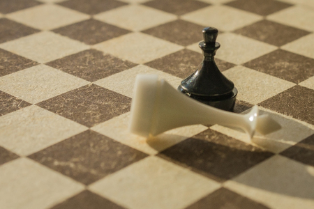 On the chessboard, a black pawn triumphed over the white king. Unexpected defeat, disappointing loss. Warm tones, vignetting.