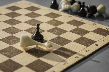 A chess field and black and white figures. The pawn beat the king. The outcome of the game, an unexpected denouement. Muted tones, macro shooting.