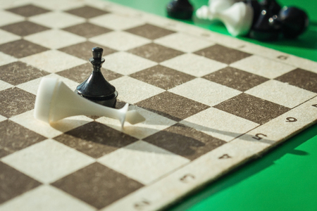 A black pawn on the chessboard beats the white king. Unexpected victory, ineffective forces. Green background, the background is blurred. Lateral solar illumination.