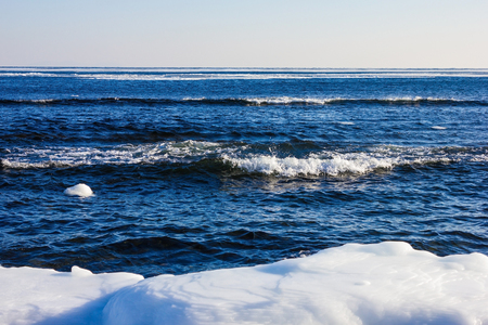 Northern latitudes, seascape. On the shore of white ice. Cold climate, north. Dark blue water, small waves.