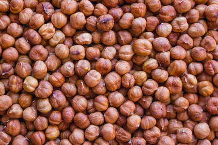 Brown background of large, round hazelnut kernels. Proper nutrition, health care, a healthy lifestyle. Food of vegetarians, athletes.