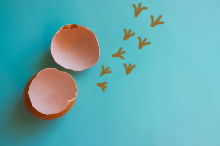 On a blue background there are two egg shells. Near painted traces of chicken. Break your shell, get out of the comfort zone, leave the familiar environment.