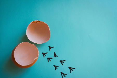 Empty eggshell, next to a chain of tracks. Everything has its time, its own way, growing up of children. Blue background, top view. The picture is made by the author.