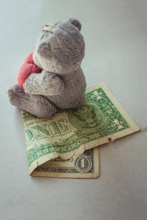 A small toy teddy bear sits on one dollar. Lack of money for a child, low alimony, inadequate state support for families with children. Vertical arrangement. A toy of mass production.
