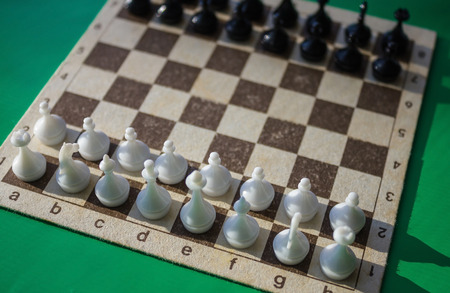 Chessboard, black and white figures are placed in the starting position. Confrontation, tension, minute before the battle. View from above.