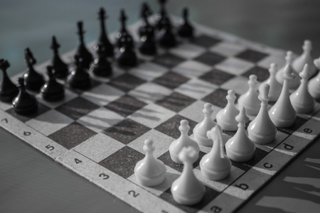 A game of chess, the initial stage. Evaluation of the enemy, waiting for the first move. Opponent, counterpart, the other side. Black and white colors, daylight.