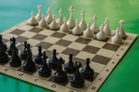 Black and white figures are placed on a chessboard. Waiting for the first move of the enemy, willingness to fight. Daylight, the background is blurred.