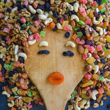 A womans face is lined with a fruit mixture. Funny expression, bright colors. A healthy diet, a healthy snack. Daylight.