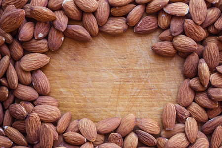 Peeled nuts, almonds. In the center there is a vintage wooden surface, scratches, marks from the knife. Dietary nutrition, sports diet, a source of vegetable protein. Banque d'images