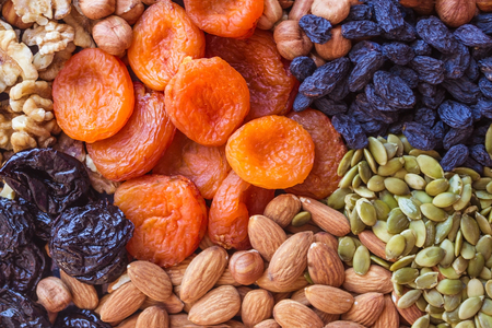 Abundance, useful natural food, nourishing snack. Nuts, dried apricots, raisins, prunes and pumpkin seeds. Sources of vegetable protein. View from above.