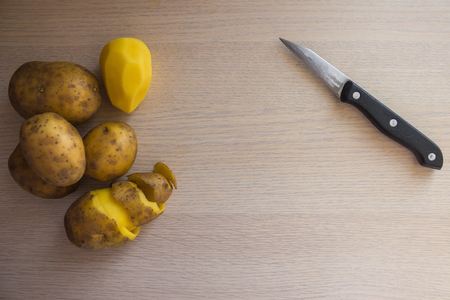 Yellow raw potatoes on the kitchen table, next to a knife for cleaning vegetables. Home cooking, cooking simple, traditional dishes. Natural product.