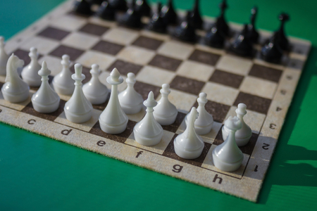 Figures on the chessboard, starting position. Minute before the fight. Evaluation of enemy forces. Green background, natural light.