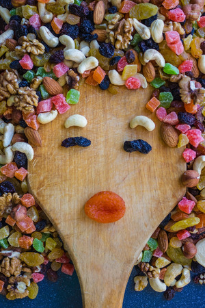 On the wooden board, slices of dried fruits and nuts lined the girls face. Bright colors, funny facial expressions. View from above. Banque d'images