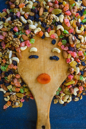 Vintage cutting board made of wood, on top mix of nuts and candied fruits. Dietary, lean food, proper nutrition, healthy snack. A funny womans face.