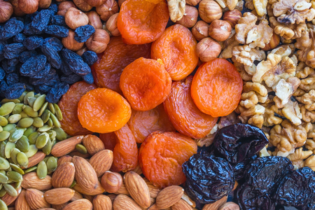 Useful food, proper nutrition. Abundance, assortment of nuts and dried fruits. In the center are orange apricots. Natural, organic product. Stock Photo