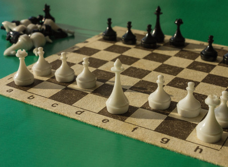 A game of chess, a white king and his pawns in the foreground. Analysis of the situation, planning for further action. Green background, side sunlight. Banque d'images