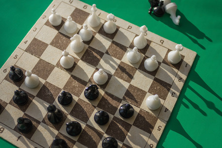 The game is in full swing. A chess field with figures. Planning a combination, further action. Waiting for the opponents move. Top view, green background. Banque d'images