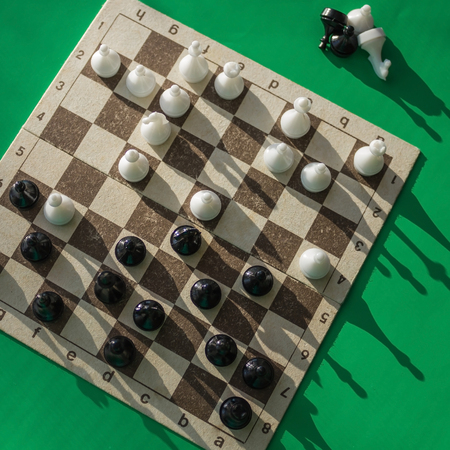 Confrontation between the two sides, the chess game, the middle of the match. Complex combination, calculation of the next move. Green background, top view.