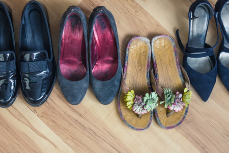 Refusal from the dress code, freelancing, downshifting, life outside the standards. A row of womens shoes, in front of colored slippers. Comfort, rest, vacation. Banque d'images