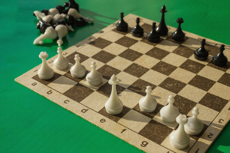 On the chessboard are black and white figures, the height of the game. Part of the figures have already left the game, the ranks have thinned out. Analysis, decision making. Green background. Foto de archivo