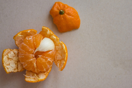 In orange mandarin, one slice of garlic. Bitter in sweet, a fly in the ointment, an insider, a stranger. Top view, light background.