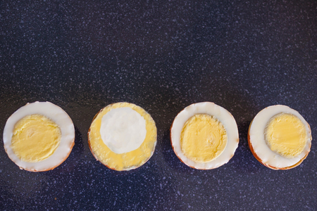 Four boiled eggs, one is different from all. Unlike, strange, not like everyone else. Odd man out. View from above.