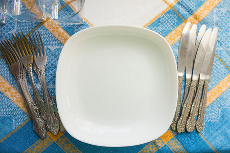 A lot of cutlery, glasses on the kitchen table. Preparation for the reception of guests, home furnishings. Blue tablecloth, daylight, top view. Banque d'images