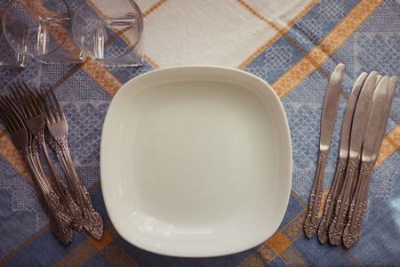 Plates, forks and knives, glasses on a linen tablecloth. Muted tone, vintage style. Home furnishings, comfort, hospitality.