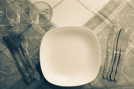 Cutlery on a linen tablecloth. Retro style, muted tone. Bon Appetit! Hospitality, comfort, homemade food. View from above.
