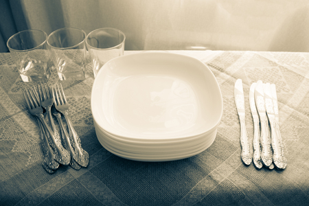Glasses, a stack of plates, knives and forks on a linen tablecloth. Kitchen table, preparation for the reception of guests. Retro style, natural lighting.