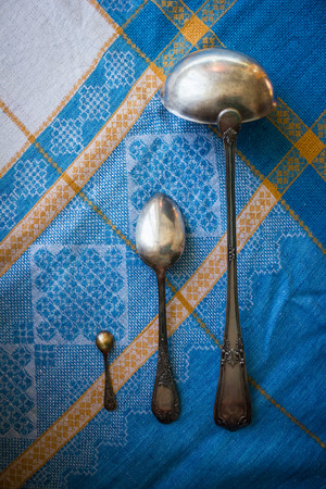Ancient silver spoons of different sizes. Household, kitchen, dining utensils. A blue linen tablecloth. View from above.