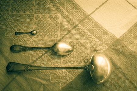Cutlery, antique silver on a vintage tablecloth of linen. Household, cooking at home, old utensils, kitchen. Retro sitel, vignetting, top view.