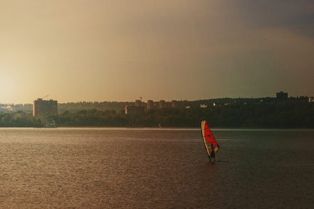Doing sports, windsurfing in the city. The man under the orange sail moves on the water surface. In the background is a modern city landscape.