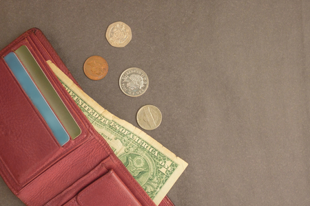 A dollar is sticking out of a red purse, alongside small coins. The last money, bankruptcy. Muted tone, gray background.