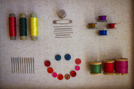 Wooden, cardboard and metal bobbins with colored thread for sewing. Near needles for manual and machine stitching, buttons for clothes.