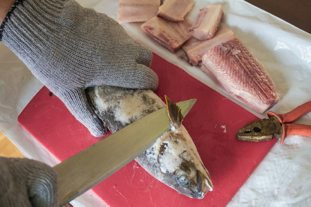 Cutting frozen fish, salmon, on fillets. Red kitchen board, hands in special gloves. Next pliers for skinning. Kitchen of the indigenous peoples of the North. Banque d'images