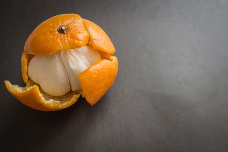 Unpleasant surprise, disappointment, vain hopes. Under the skin of a sweet mandarin, bitter garlic was hidden. Dark background, daylight.