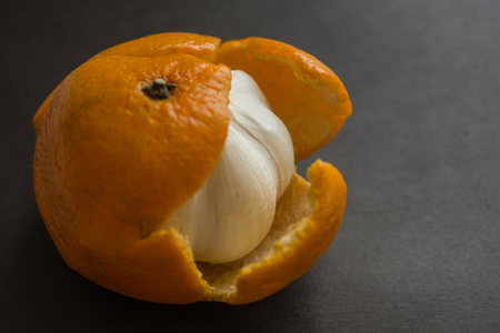 In the tangerine skin hides the bitter garlic. Deceived expectations, trickery, pretense. Dark background, side lighting.