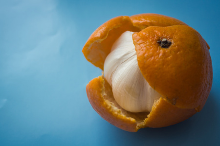 Garlic in a tangerine skin, a pretender, a hypocritical man. Hiding the bitter truth, deception, distortion of reality. Blue background, vignetting. Stock Photo