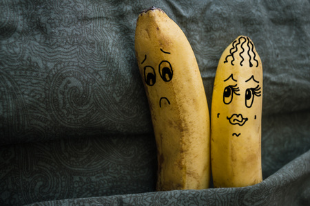 Two bananas, lovers, in bed. A woman wants sex, a man turns away, refuses, can not. Sexual problems, dissatisfaction. The picture is made by the author. Banque d'images